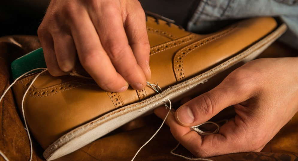 young shoemaker in workshop making shoes