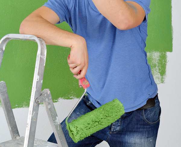 man paint in blue and green color white wall of new home